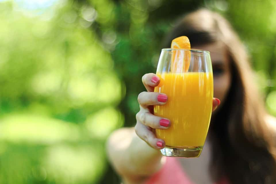 Lady holding a glass full of fresh citrus juice